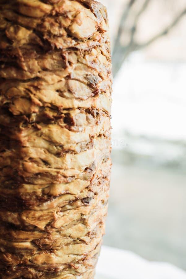 Cottura shawarma e della ciabatta in un caffè Un uomo in carne dei tagli dei guanti eliminabili su uno spiedo fotografia stock