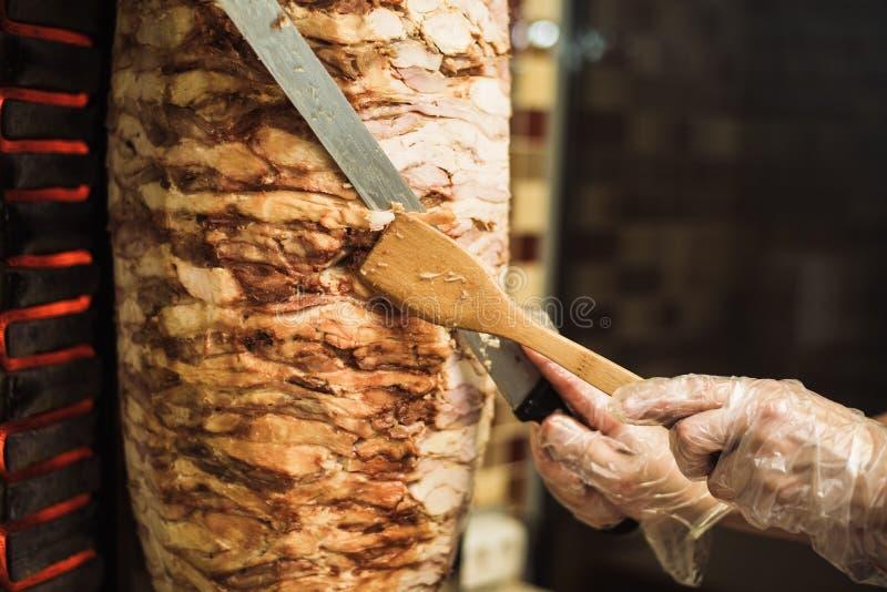 Cottura shawarma e della ciabatta in un caffè Un uomo in carne dei tagli dei guanti eliminabili su uno spiedo fotografia stock libera da diritti