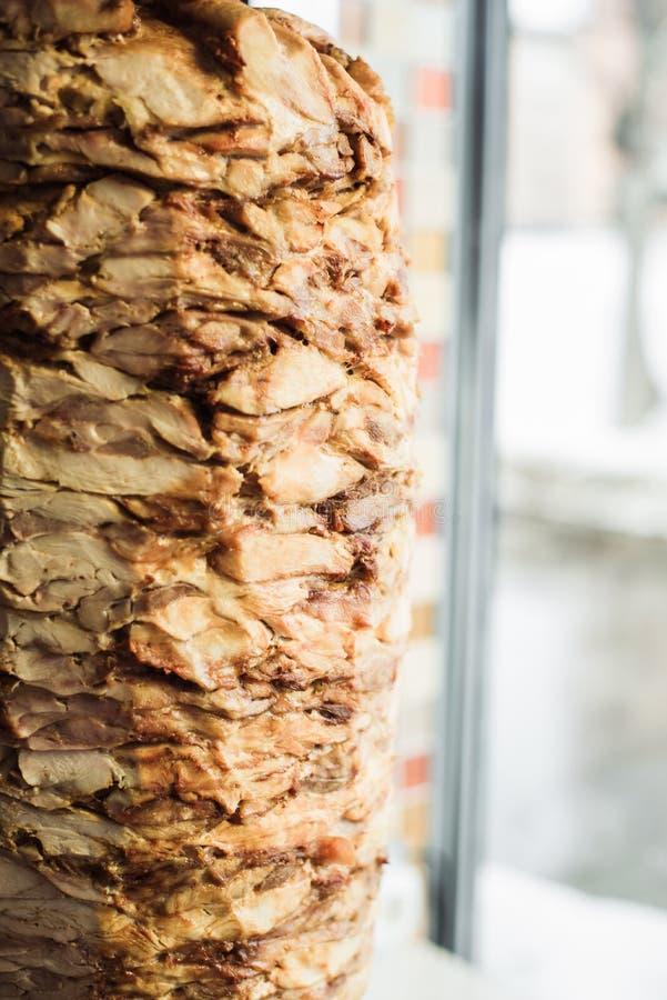 Cottura shawarma e della ciabatta in un caffè Un uomo in carne dei tagli dei guanti eliminabili su uno spiedo fotografie stock