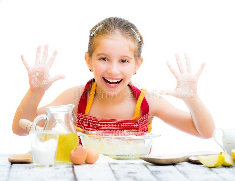 Cottura sveglia della bambina sulla cucina immagini stock