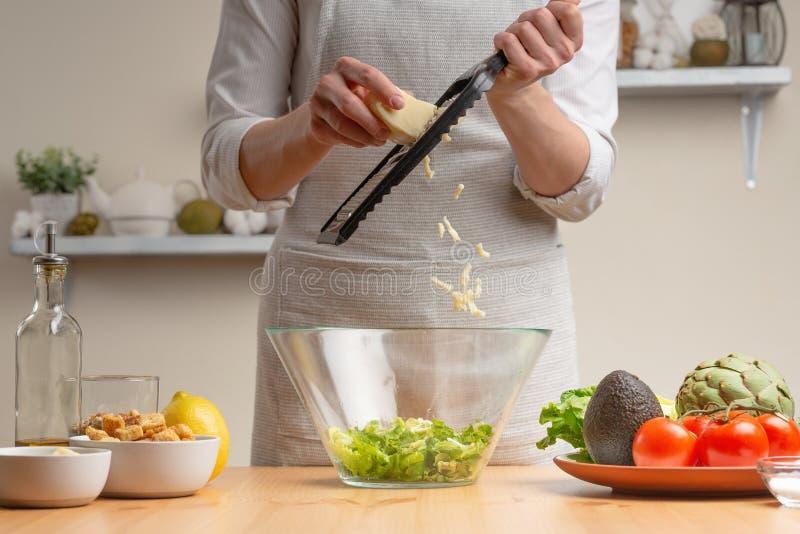 cottura Un cuoco unico versa la mozzarella o il feta, nel corso di un'insalata vegetariana nella cucina domestica Fondo leggero immagine stock