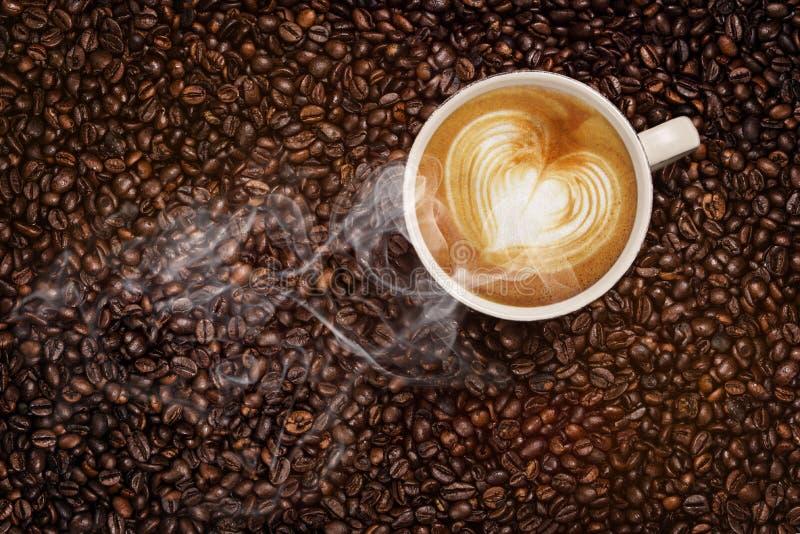 Cottura a vapore della tazza di caffè sui chicchi di caffè fotografie stock