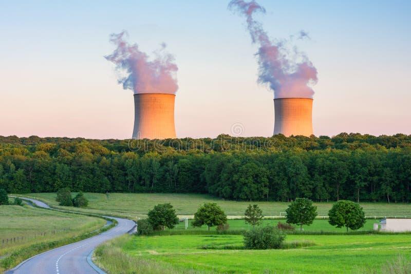 Cottura a vapore delle torri di raffreddamento nella centrale atomica intorno al tramonto fotografia stock