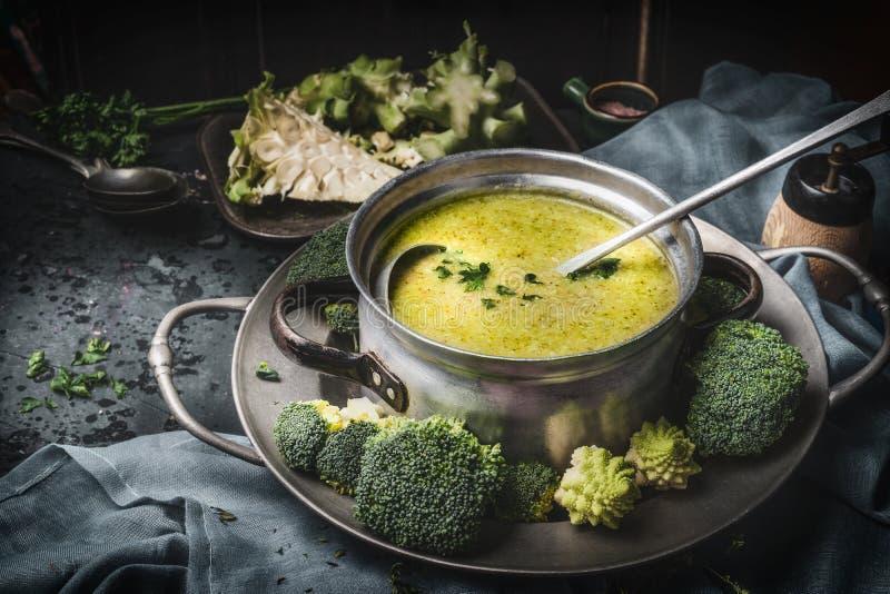Cottura vaso con il romanesco verde e dei broccoli minestra e siviera sul tavolo da cucina rustico scuro Nutrizione sana di dieta fotografia stock