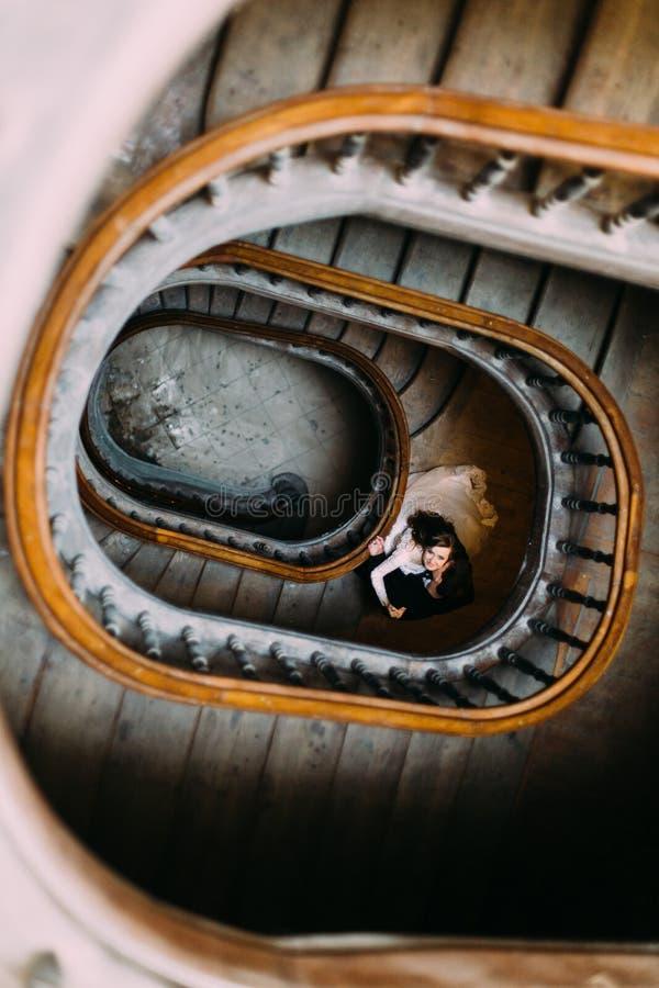Cou de baiser de jeunes mariées de marié beau beau sur de vieux escaliers en bois à l'intérieur, vue supérieure photos libres de droits