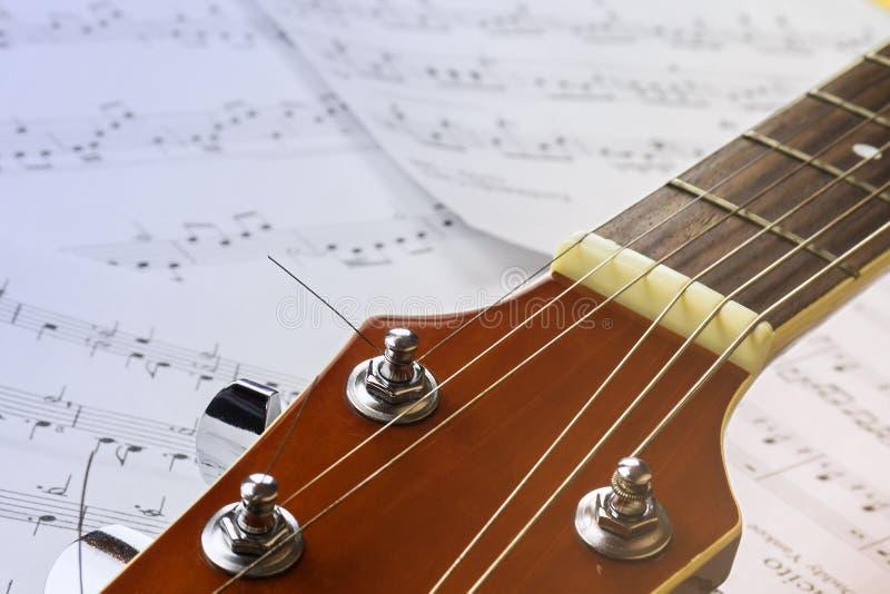 Cou de guitare sur le fond des feuilles avec des notes images stock