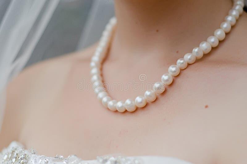 Cou de jeune mariée avec de la ficelle des perles photographie stock