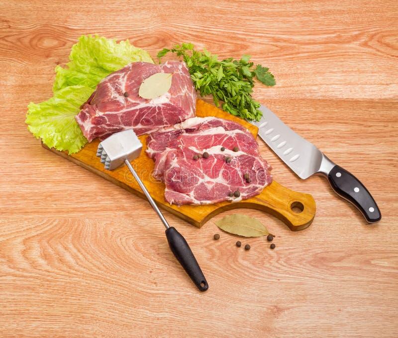 Cou de porc sur la planche à découper, l'attendrisseur de viande et le couteau de cuisine photo libre de droits