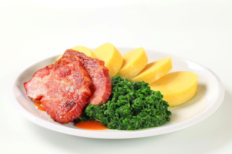 Cou fumé de porc avec des boulettes et des épinards de pomme de terre photo stock