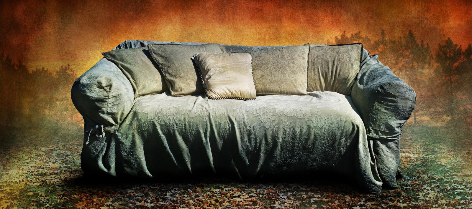 Couch. An old grunge couch on a leafy surface with a landscape background. Concept for an interview royalty free stock image
