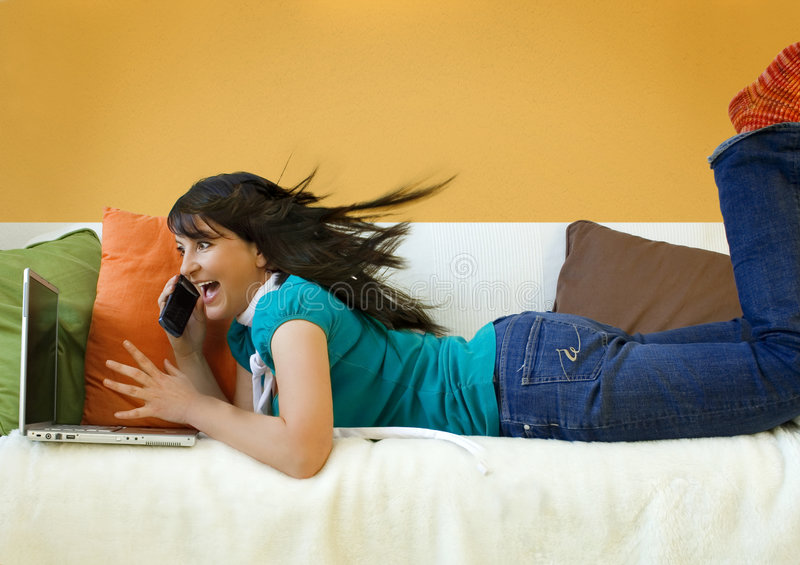 Excited Woman on Sofa with Phone and Laptop royalty free stock photography