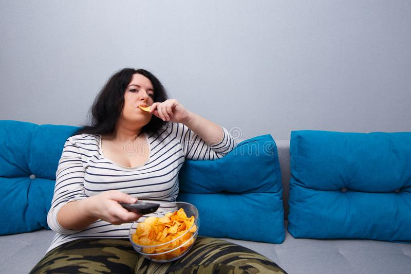 Couch potato overweight woman sitting on the sofa, eating chips stock photography