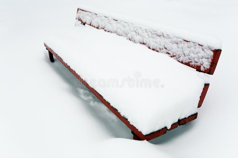 Couche épaisse de neige sur le banc photos stock