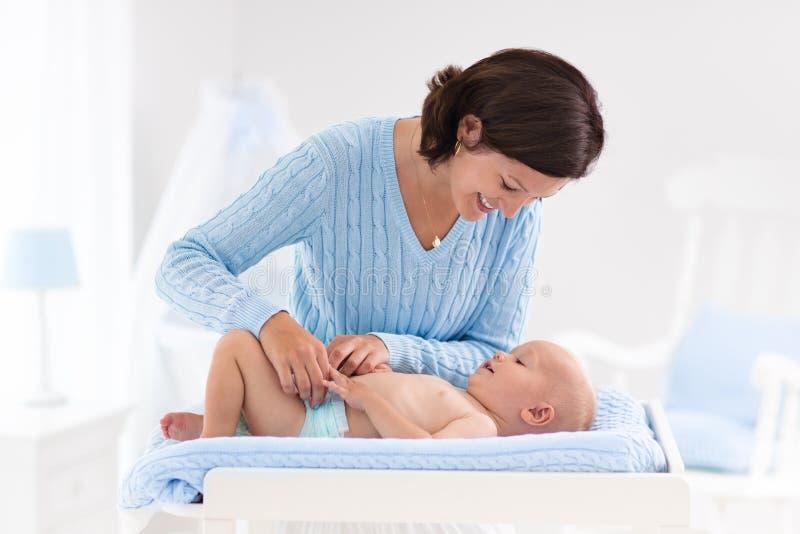 Couche-culotte changeante de mère au bébé garçon images libres de droits