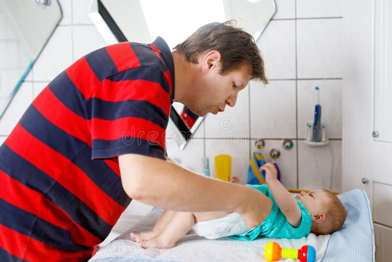 Couche-culotte changeante de père affectueux de sa fille nouveau-née de bébé images libres de droits