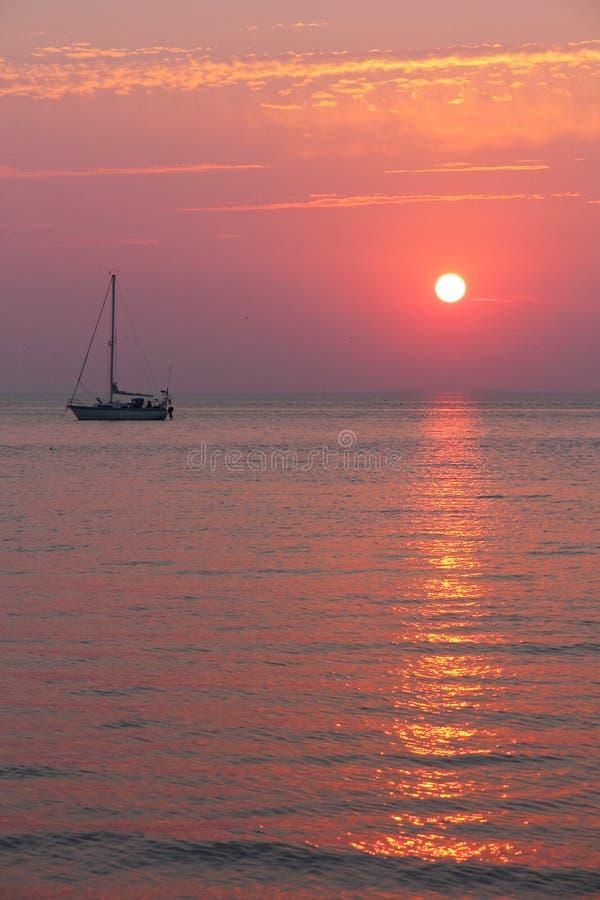 Coucher de soleil et voilier chauds photographie stock libre de droits