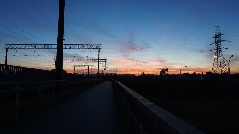 Coucher du soleil à l'arrêt de train avec le beau ciel bleu profond et les nuages rouges wide photographie stock libre de droits
