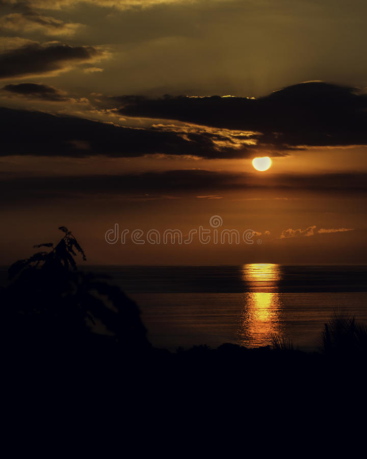 Coucher du soleil à la mer avec les silhouettes foncées photo stock