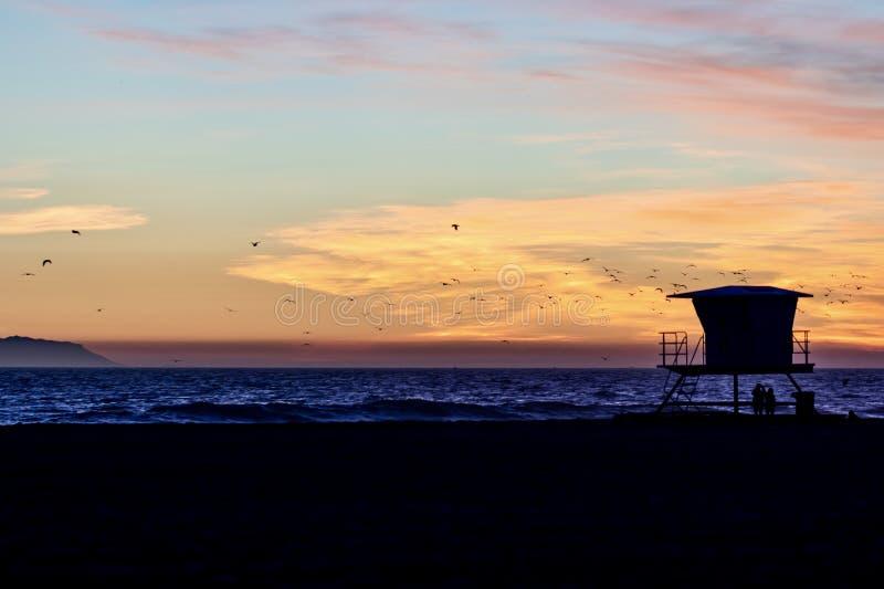 Coucher du soleil à la plage avec des silhouettes image stock
