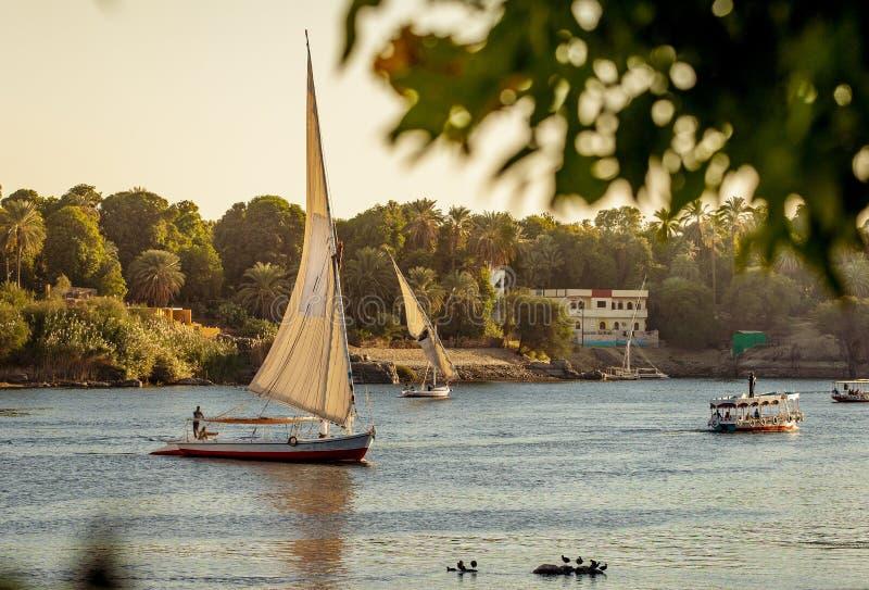 Coucher du soleil égyptien scénique sur le Nil avec des bateaux de Felluca à Louxor Egypte photographie stock libre de droits