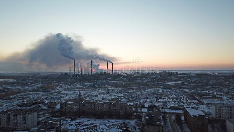 Coucher du soleil épique sur le fond d'une usine de tabagisme Le soleil rouge avec les rayons lumineux dépasse les usines et le b photographie stock