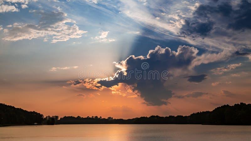Coucher du soleil étonnant au lac d'été avec les nuages dynamiques photographie stock libre de droits