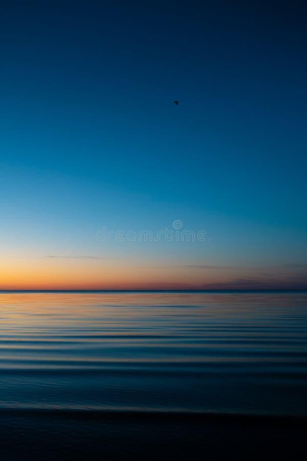 Coucher du soleil étonnant vif dans les pays Baltes - le crépuscule en mer avec l'horizon illumine par le soleil photos stock