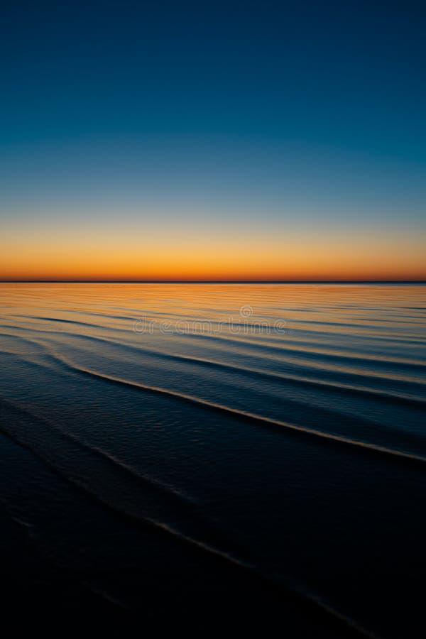 Coucher du soleil étonnant vif dans les pays Baltes - le crépuscule en mer avec l'horizon illumine par le soleil image libre de droits