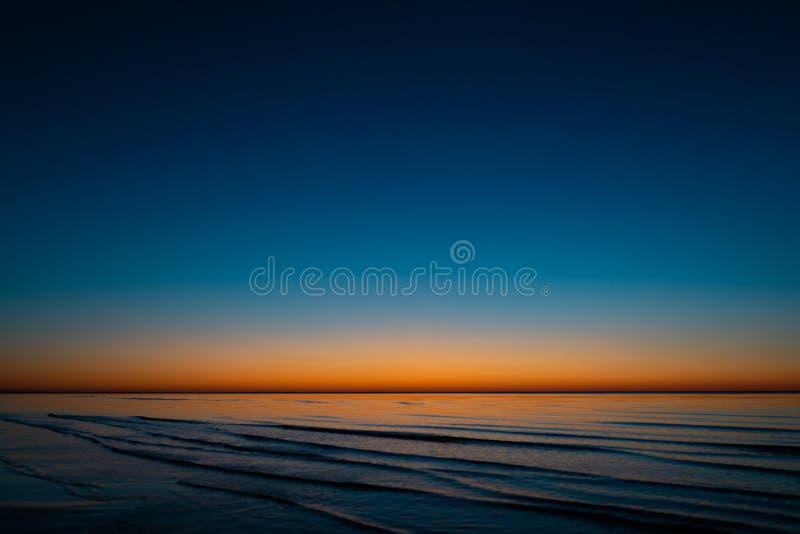 Coucher du soleil étonnant vif dans les pays Baltes - le crépuscule en mer avec l'horizon illumine par le soleil images libres de droits