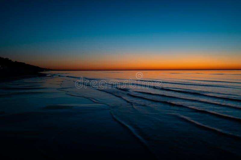 Coucher du soleil étonnant vif dans les pays Baltes - le crépuscule en mer avec l'horizon illumine par le soleil photographie stock
