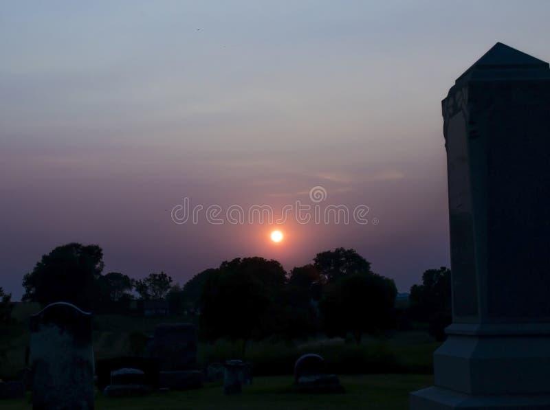 Coucher du soleil au cimetière avec la pierre tombale photos libres de droits