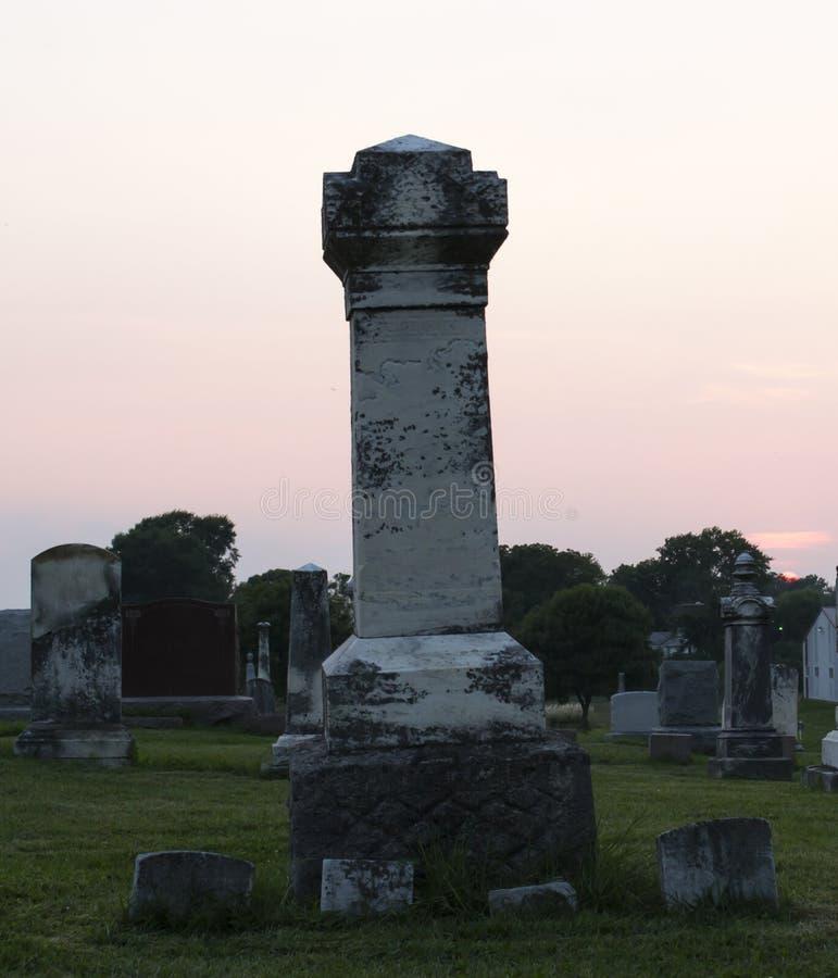Coucher du soleil au cimetière avec le sort de tombe de famille photos stock