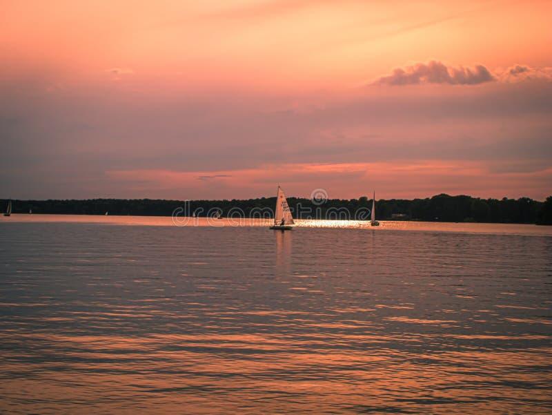 Coucher du soleil au-dessus d'un lac calme avec des bateaux à voile photographie stock