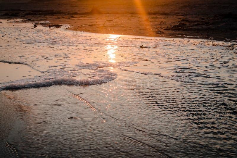 Coucher du soleil au-dessus d'une piscine de marée sur la plage photos stock