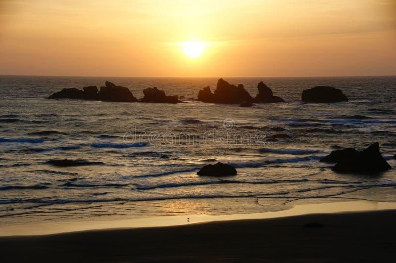 Coucher du soleil au-dessus d'une plage rocheuse images libres de droits