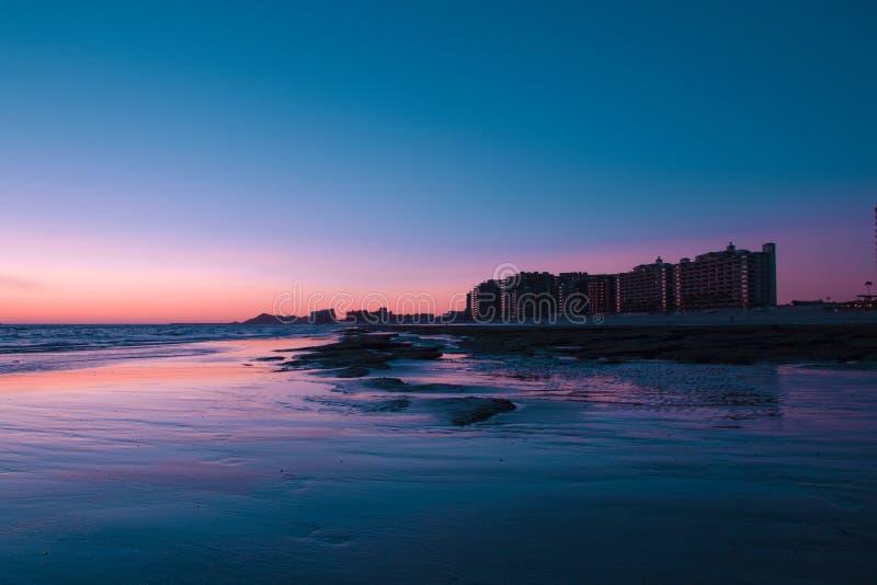 Coucher du soleil au-dessus d'une plage rocheuse dans l'avant les hôtels photos stock