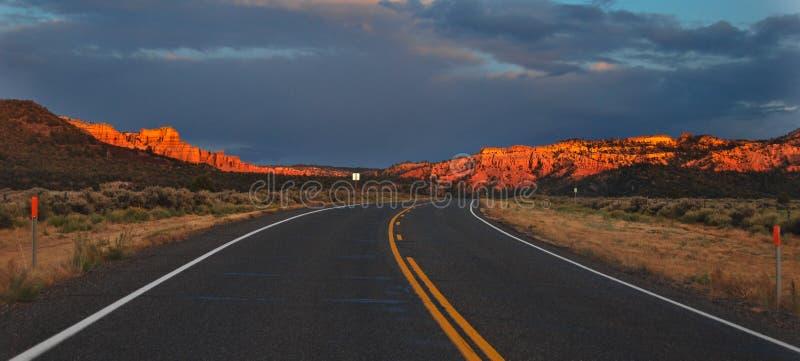 Coucher du soleil au-dessus d'une route de désert photo stock