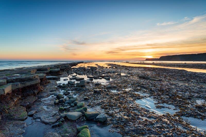Coucher du soleil au-dessus de baie de Kimmeridge dans Dorset photo stock