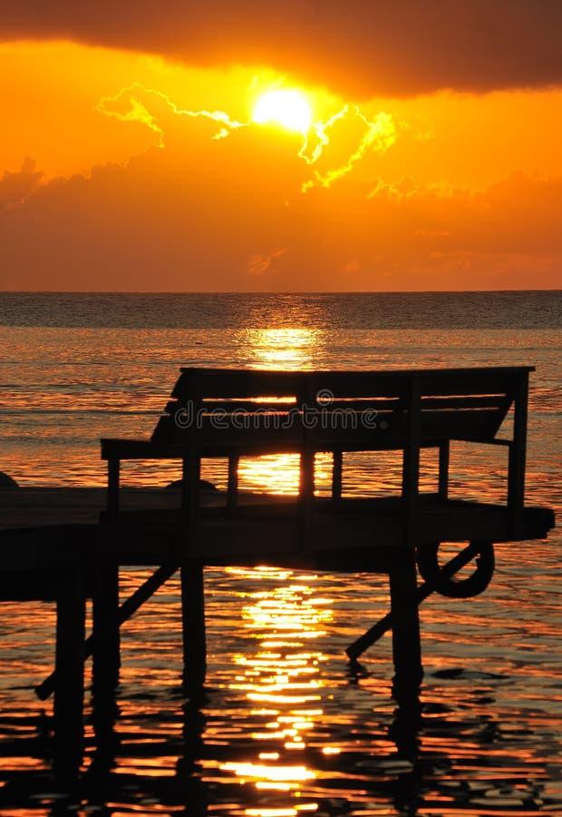 Coucher du soleil au-dessus de banc sur le pilier photos stock