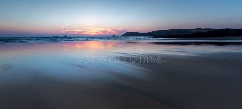 Coucher du soleil au-dessus de belle plage abandonnée, Constantine Bay, les Cornouailles photographie stock