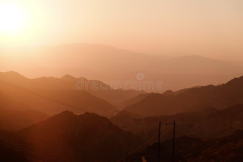 Coucher du soleil au-dessus de couche de gammes de montagne photos stock