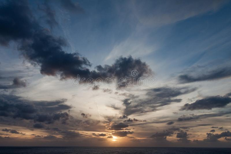 Coucher du soleil au-dessus de l'océan avec les nuages foncés photographie stock libre de droits