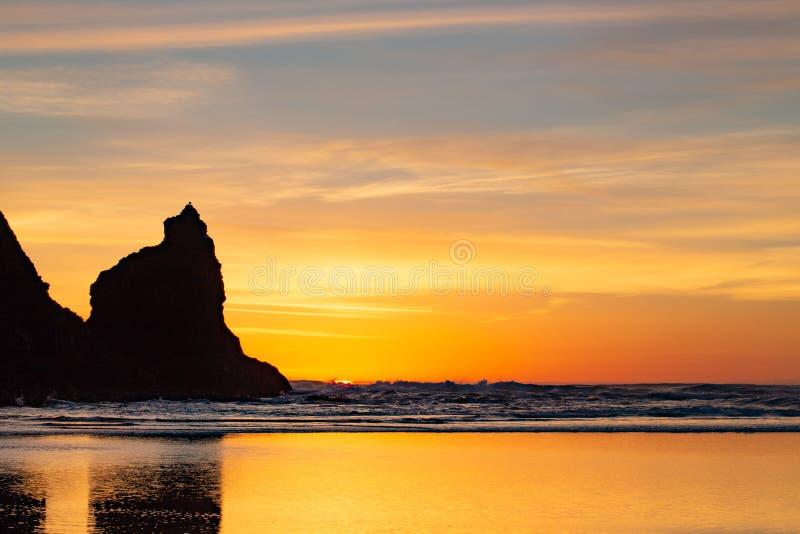 Coucher du soleil au-dessus de l'océan pacifique avec des roches silhouettées contre le ciel photographie stock libre de droits