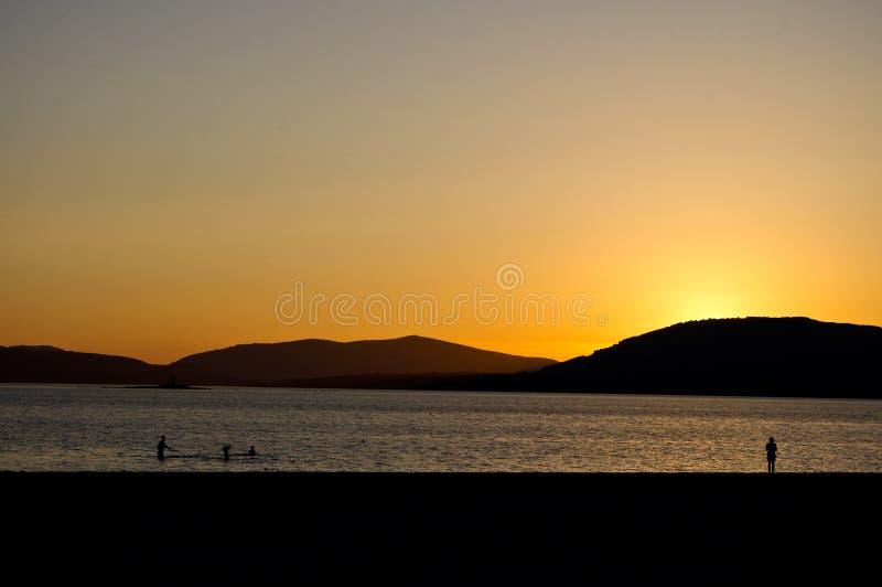 Coucher du soleil au-dessus de la mer avec des personnes photos libres de droits