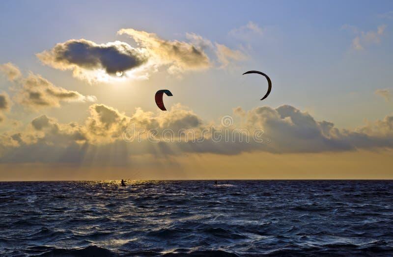 Coucher du soleil au-dessus de la mer avec des surfers de cerf-volant photo libre de droits