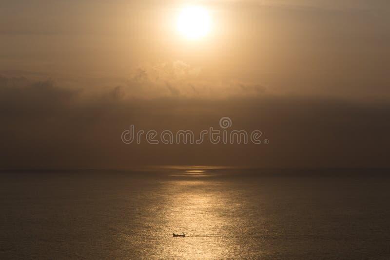Coucher du soleil au-dessus de la mer avec le bateau de dépassement photos libres de droits