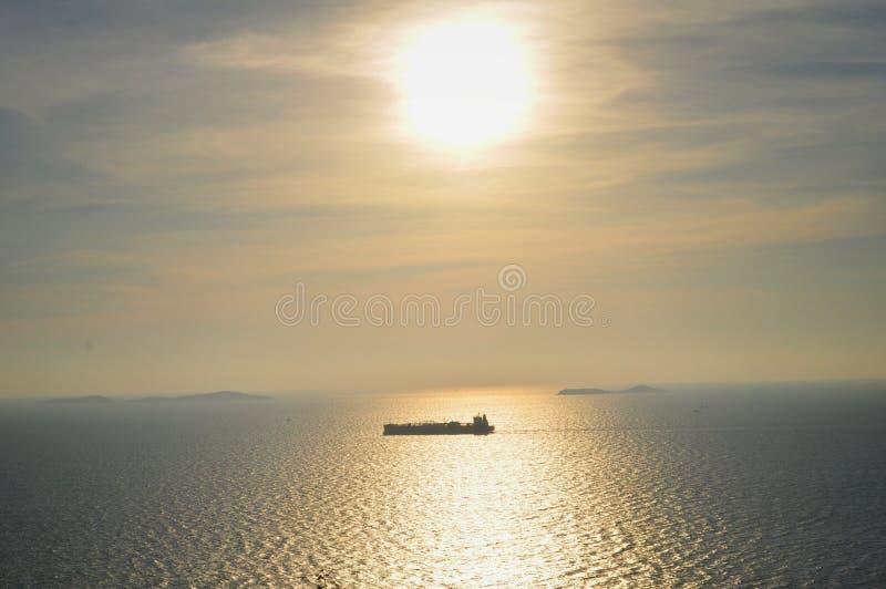 Coucher du soleil au-dessus de la mer avec un bateau photos stock