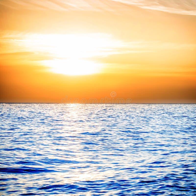 Coucher du soleil au-dessus de la mer bleue photos stock