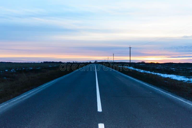 Coucher du soleil au-dessus de la route, couverte d'asphalte, qui part Des deux côtés d'un champ vide image stock