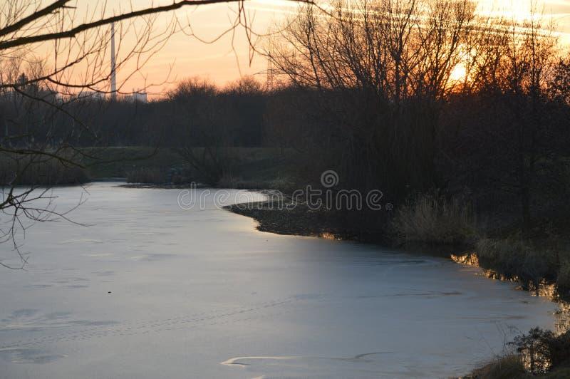 Coucher du soleil au-dessus de lac à la fin de l'hiver images libres de droits